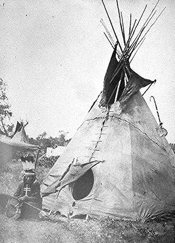 Little Big Mouth, a medicine man, seated in front of his lodge near Fort Sill, Oklahoma, with medicine bag visible from behinid the tent.